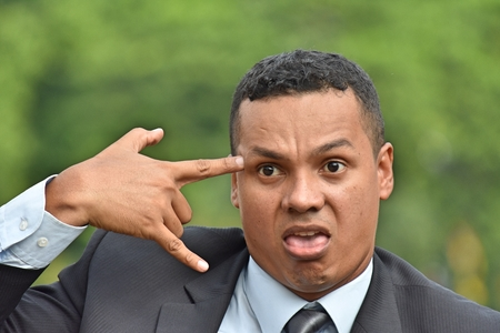 Businessman Wearing Business Suit showing suicide gesture