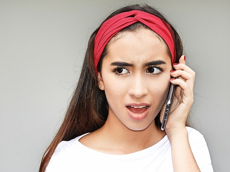 Hispanic Girl Using Cell Phone And Unhappy