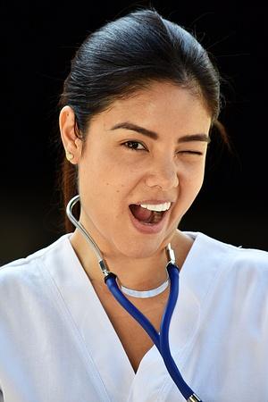 Hispanic Female Nurse Winking Wearing Scrubs Stock Photo