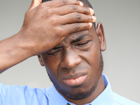 A stressful man in blue shirt and tie holding his forehead Stock Photo
