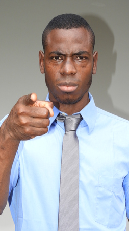 A man in blue shirt and tie pointing with his index finger