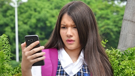 Female Student Using Cell Phone And Unhappy
