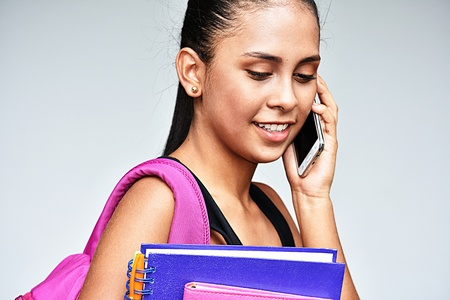 Teenager School Girl Using Cell Phone And Happy Stock Photo