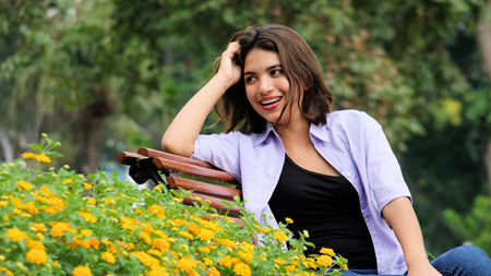 Excited Beautiful Person Sitting On Bench Stock Photo