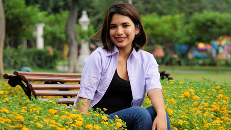 Young Female And Happiness Sitting On Bench Stock Photo
