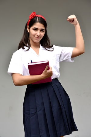 Female Teen Student Wearing Uniform Flexing Bicep Muscle Stock Photo