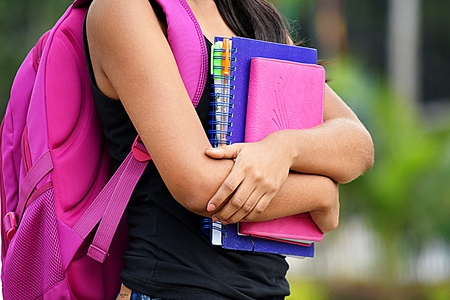 Female Student Holding Books With Backpack