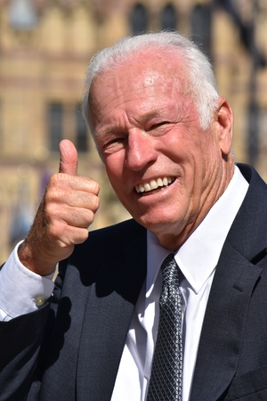 Senior Investor With Thumbs Up Wearing Suit And Tie Stock Photo