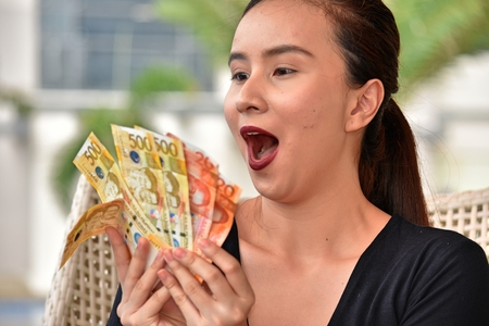 Attractive Filipina Female Counting Money Stock Photo - 109461681