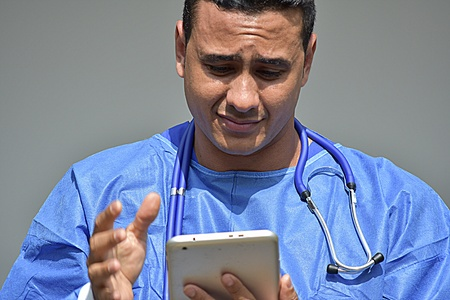 Confused Male Surgeon Wearing Scrubs