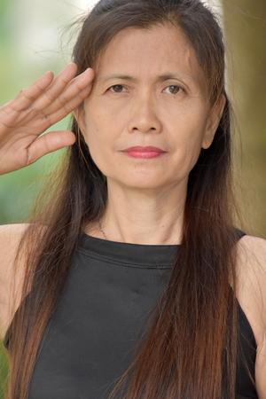 Saluting Old Minority Female Senior Stock Photo