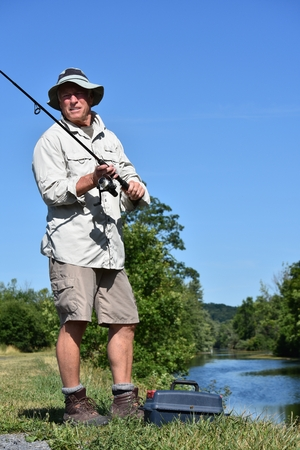 Unemotional Male Fisherman With Rod And Reel Outdoors Banco de Imagens