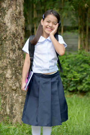 Smiling Catholic Girl Student Wearing Uniform With Notebooks