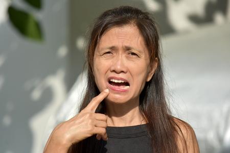 Minority Female Senior With Toothache Imagens