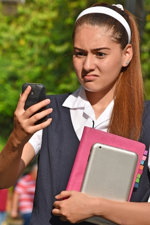 Catholic School Girl Using Cell Phone And Unhappy 写真素材