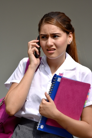 Girl Student Using Cell Phone And Unhappy Wearing School Uniform With Books