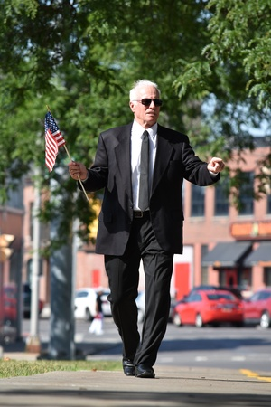 Adult Congressman Portrait Wearing Business Suit With American Flag Walking On Sidewalk
