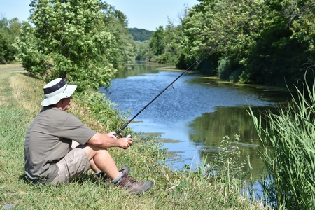 Male Fisherman Resting With Fishing Rod Outdoors