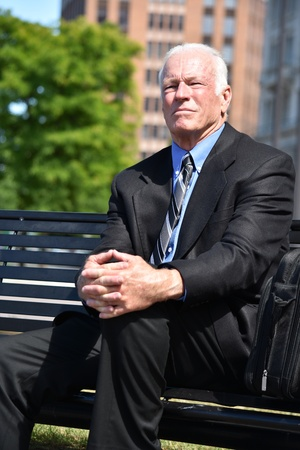 Serious Adult Senior Entrepreneur Sitting On Bench