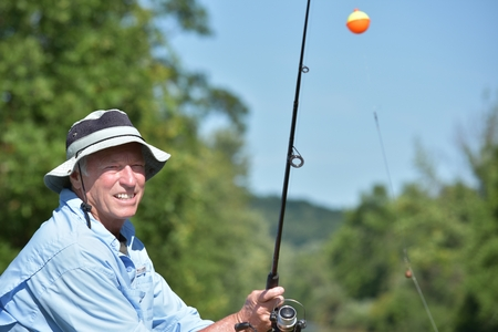 Happy Older Person With Fishing Rod Fishing Banco de Imagens