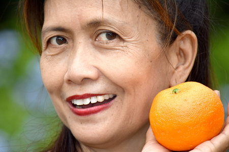 Minority Female Senior Smiling With An Orange