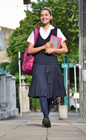 Female University Student Wearing Uniform Walking On Sidewalk Stock Photo