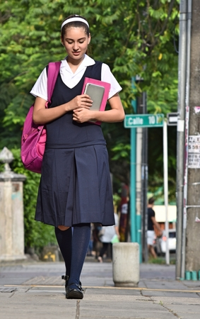 Female College Student Wearing Uniform Walking On Sidewalk