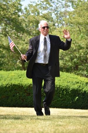 Successful Senior Male Politician With American Flag Walking