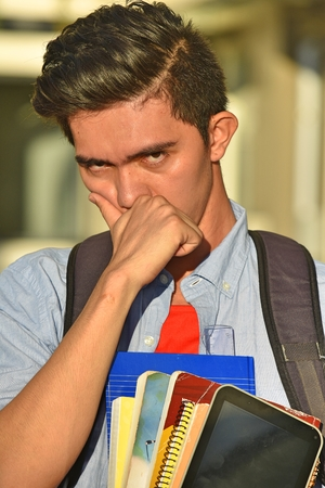 Sad Male Student With Books Imagens