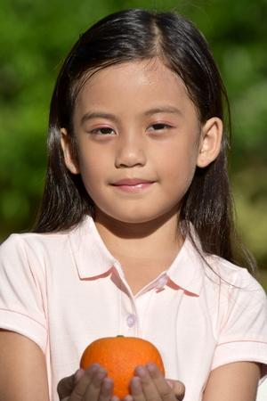 Serious Beautiful Minority Female Adolescent With Oranges Stockfoto