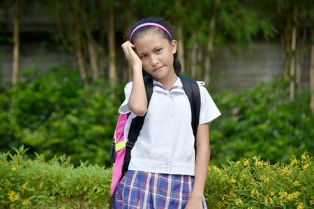 Worrisome Girl Student Wearing School Uniform With Books Banco de Imagens