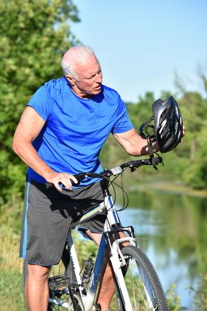 Confused Retiree Athletic Man Wearing Helmet Riding Bike