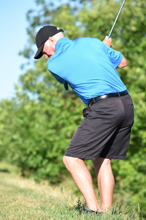 Exercising Fit Senior Male Golfer With Golf Club Swinging