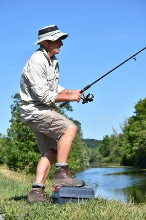 Retired Male Fisherman Standing With Rod And Reel Fishing