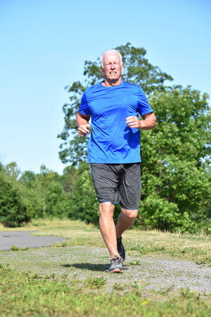 Glücklicher männlicher Senior, der im Park joggt