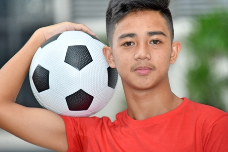 Unemotional Male Athlete With Soccer Ball 스톡 콘텐츠