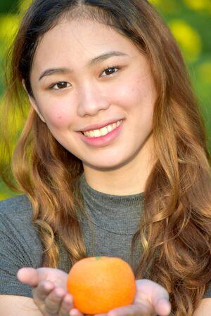 Filipina Female Smiling With Fruit Stock Photo
