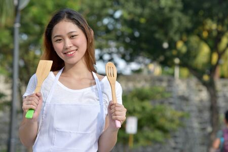 Happy Beautiful Asian Female Cook Chef Wearing Apron With Utensils Stock Photo