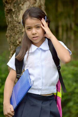 Thoughtful School Girl Wearing School Uniform With Books