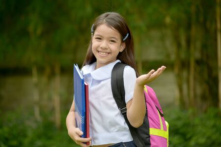 Indecisive Young Filipina Person Wearing School Uniform With Books Standard-Bild