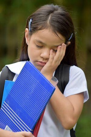 Bambino studente diversificato cattolico depresso che indossa l'uniforme scolastica con i quaderni