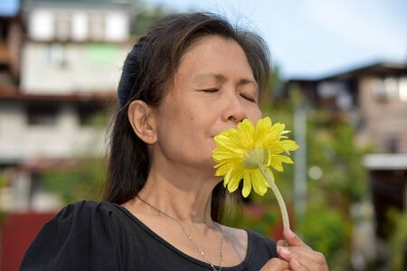 Filipina Female Senior And Poverty Smelling Flowers