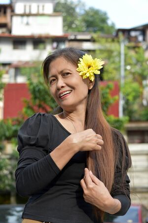 Happy Retired Asian Female Senior With A Flower