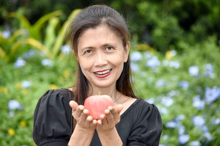 Happy Female Senior With An Apple
