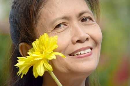 Diverse Female Senior Smiling With A Daisy