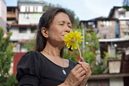 A Woman And Poverty Smelling Flowers