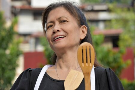 Happy Senior Filipina Person Wearing Apron With Utensils 写真素材