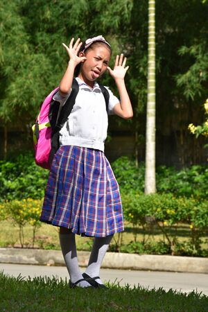Young Female Student Making Funny Faces Wearing School Uniform