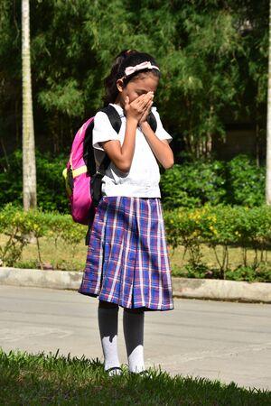 Depressed Minority Person Wearing Uniform With Books 写真素材 - 129903520