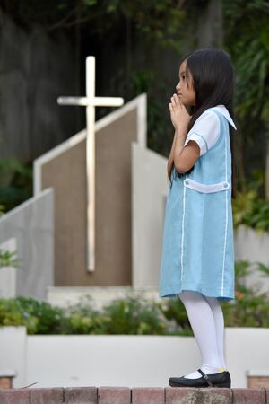 Religious Asian Tween In Prayer At Church